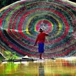 لقطة رائعة لصياد صيني يلقي شبكته الملونه