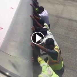 بالفيديو: رجال يدفعون طائرة.. والركاب يصورون