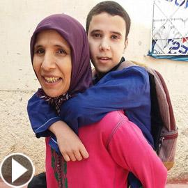 فيديو مؤثر.. أم مغربية تحمل ابنها المعاق يوميا على ظهرها إلى المدرسة!