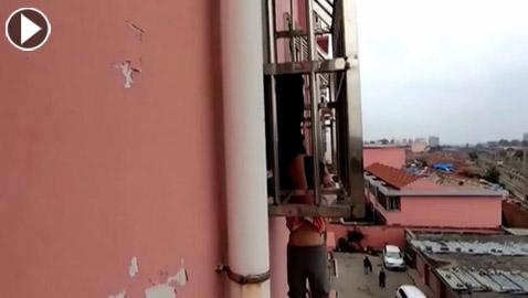 طفل يتدلى من نافذة بمبنى شاهق وصرخاته تلفت انتباه المارة